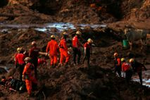 Members of a rescue team search for victims after a tailings dam owned by Brazilian mining ...