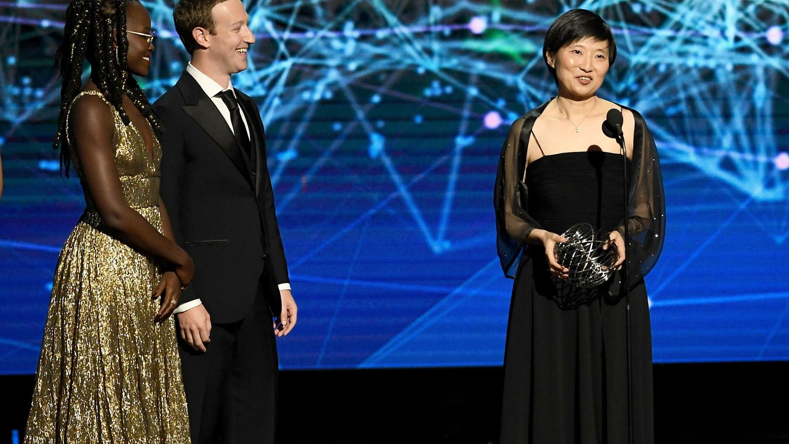 Lupita Nyong'o and Mark Zuckerberg stand with Xiaowei Zhuang, winner of the 2019 Breakthrough Prize in ...
