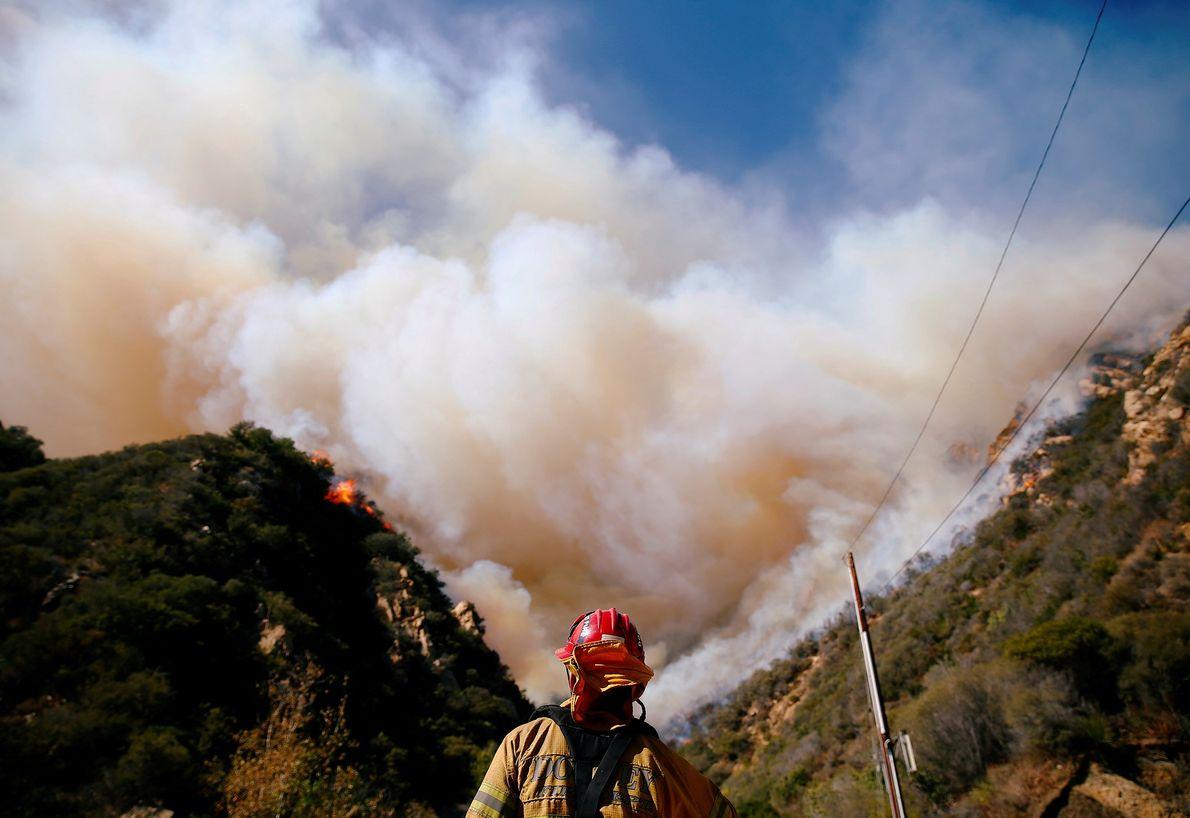 Firefighters battle the Woolsey Fire as it burns through Malibu, California.