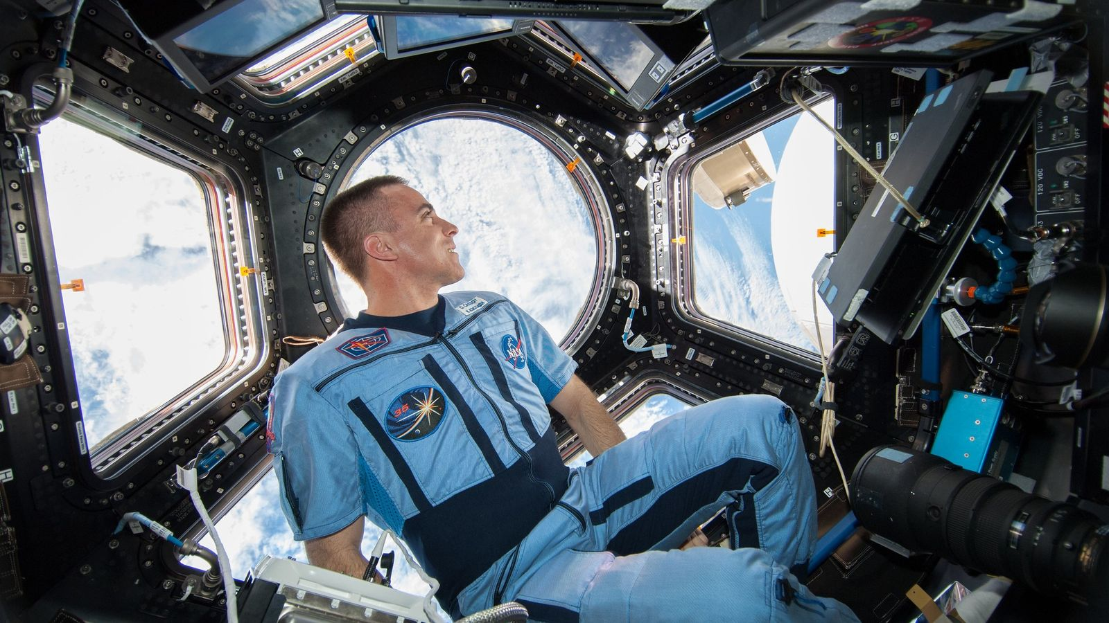 NASA astronaut Chris Cassidy gazes out the cupola of the International Space Station in August 2013, ...