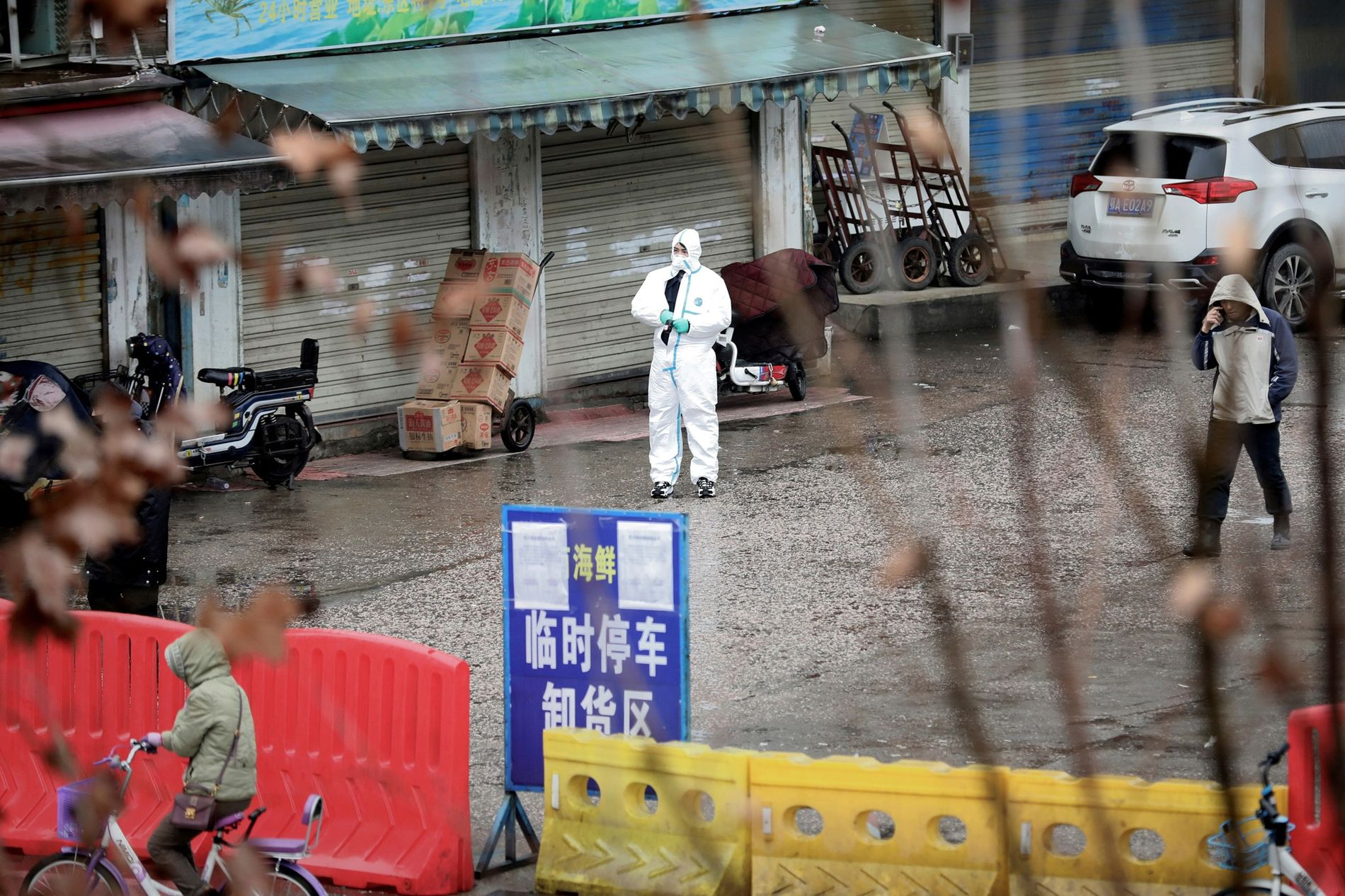 A worker stands in protective gear at the closed seafood market in Wuhan, China, thought to ...
