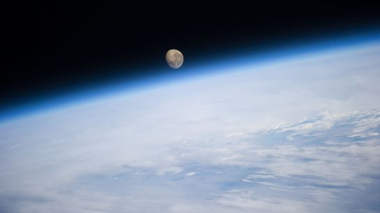 The moon sets over the Earth, in a view from the International Space Station.