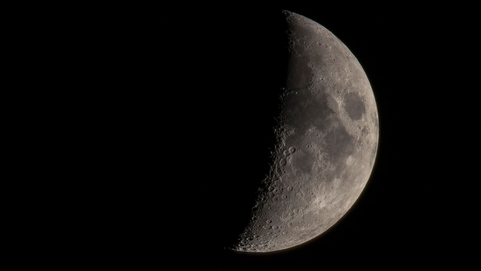 A view of the moon through a telescope showcases the many well-preserved craters and dark lava ...