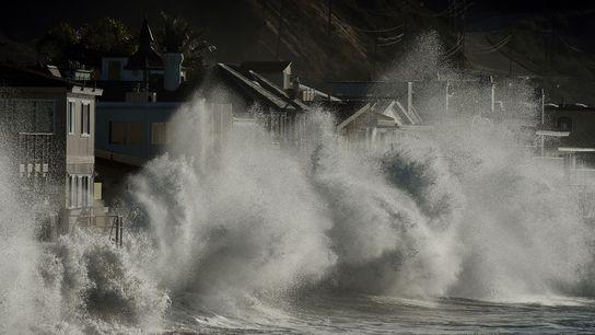 Storm waves crash onto seaside houses at Mondos Beach, California, on January 12, 2016, during a ...