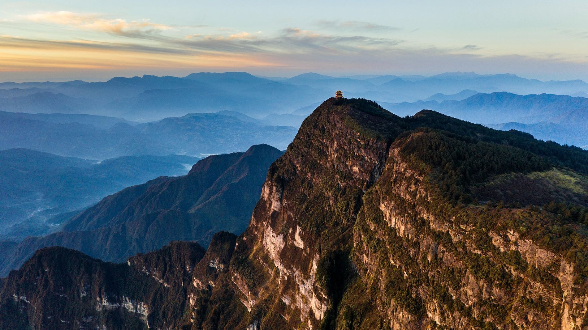 A temple sits perched on Emeishan Mountain in Sichuan Province, China. The surrounding countryside includes the ...