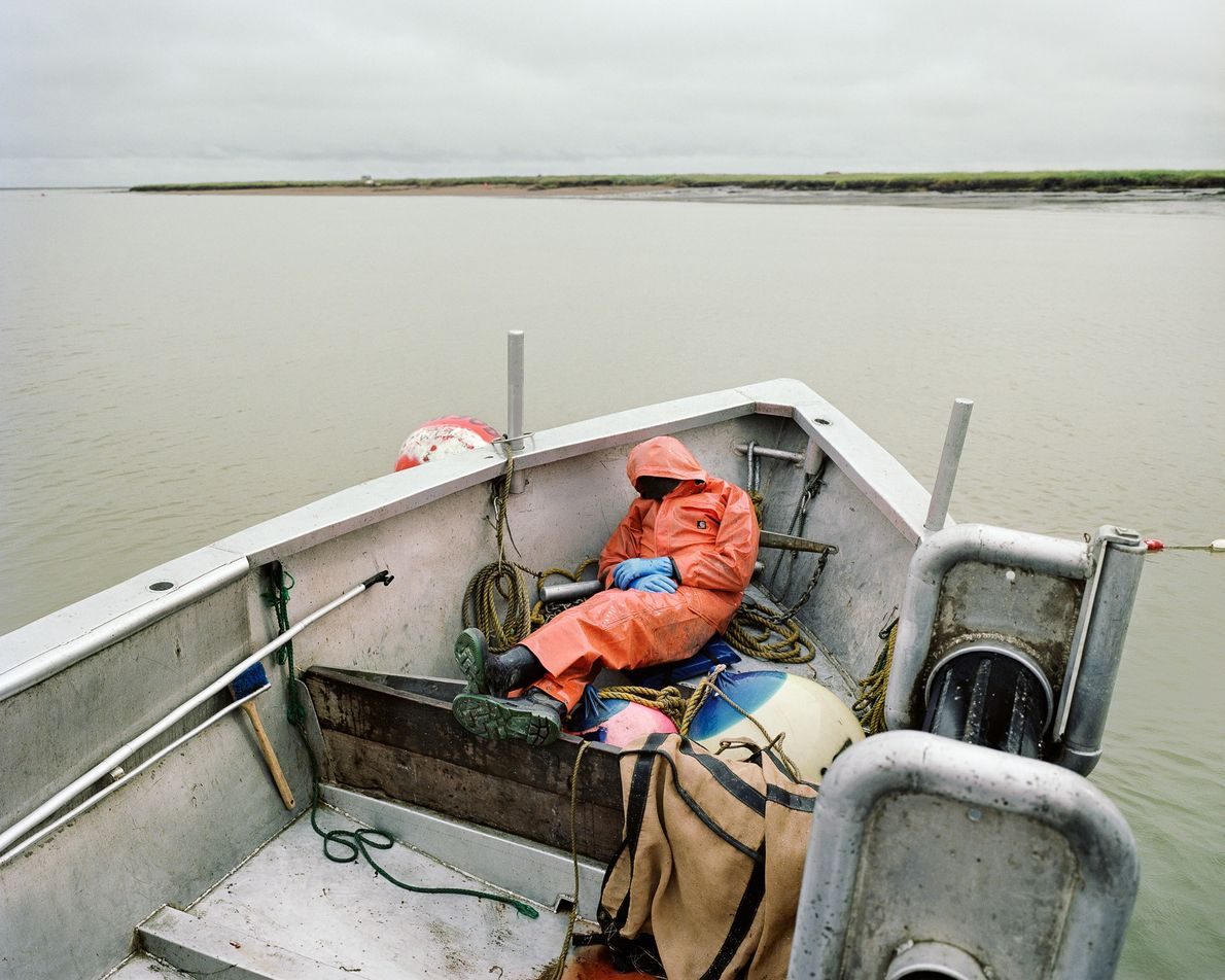 An exhausted fisherman takes a nap on a commercial fishing skiff in Bristol Bay, Alaska.  ...