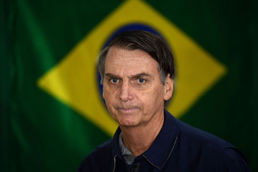 Bolsonaro, leader of the right-wing Social Liberal Party, stands before the Brazilian flag on election day.