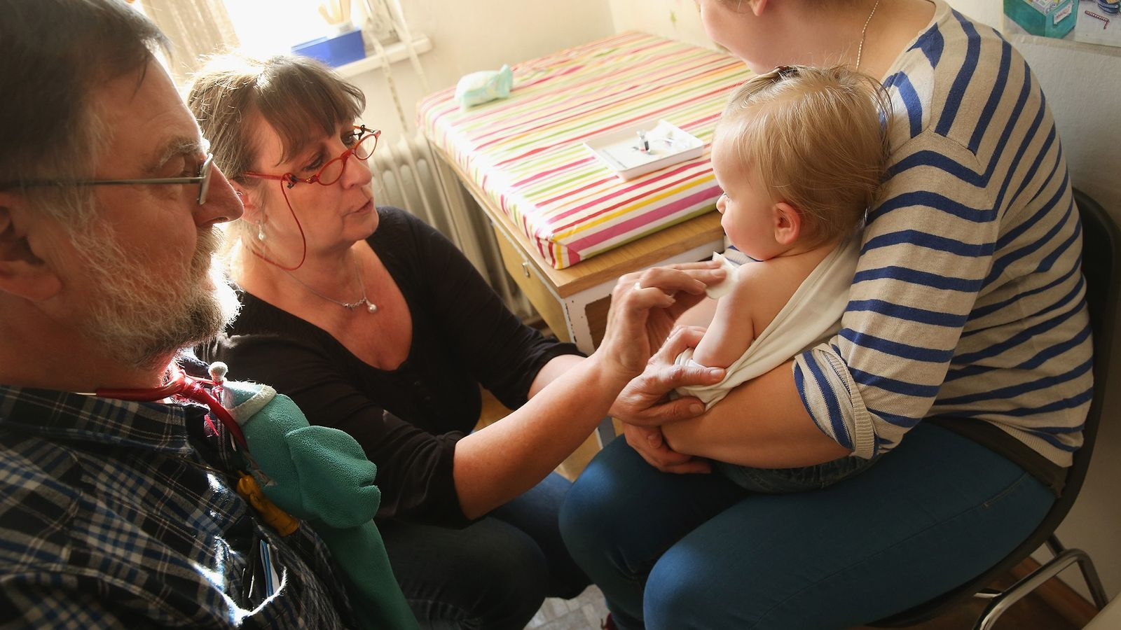 A doctor's assistant prepares 11-month-old Tijana for a vaccine against measles, rubella, mumps, and chicken pox ...