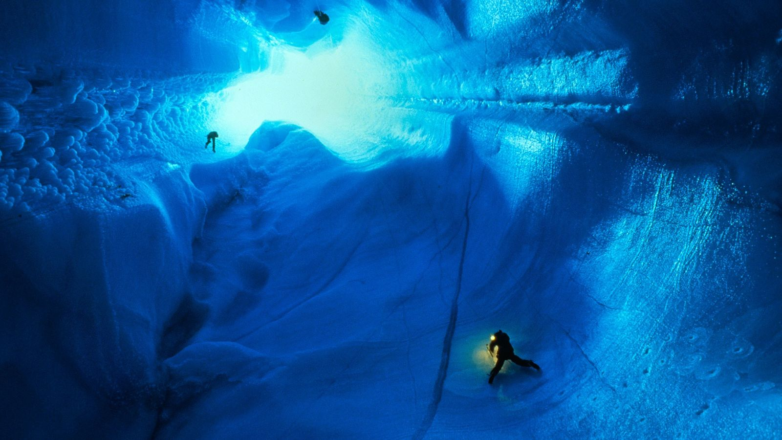 Climbers descend several hundred feet into an ice sheet in Greenland, where they hope to plumb ...