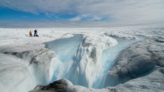 Researchers look at meltwater at the edge of the Greenland ice sheet.