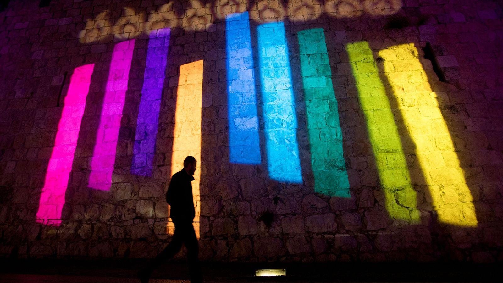 On the walls of Jerusalem's Old City, a colorful menorah lights up the night during Hanukkah.