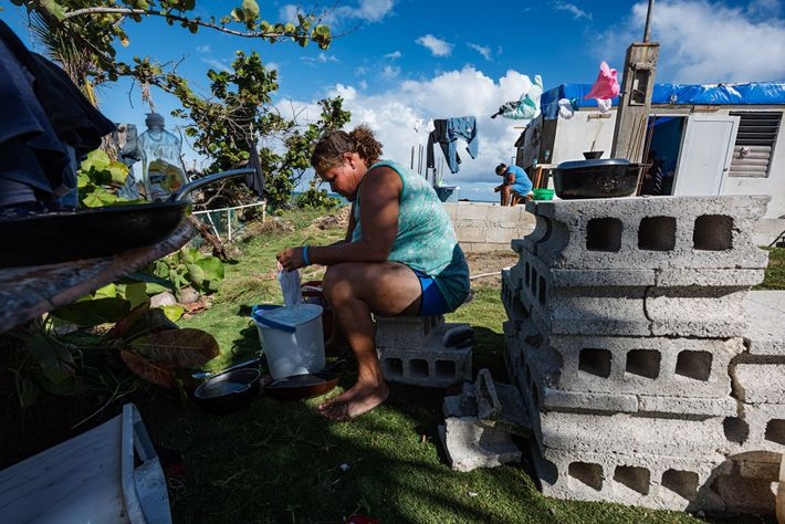 Yasmin Morales Torres, 41, washes laundry by hand in her yard in Playa El Negro, a ...