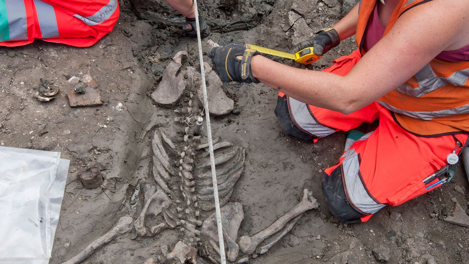Archaeologists in London study the skeleton of an adult male in his early thirties whose remains ...