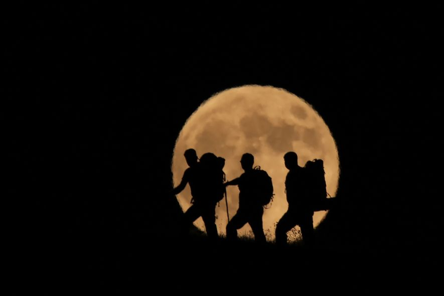 The full moon rises behind silhouetted climbers on Mount Artos in Turkey's Van Province on July ...