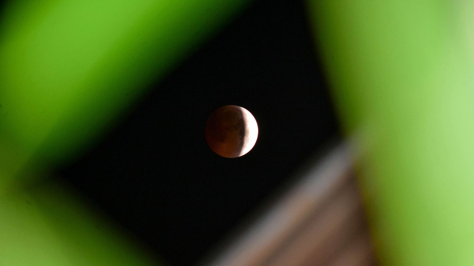 A partial lunar eclipse darkens the face of the moon as seen from Srinagar, India, in ...