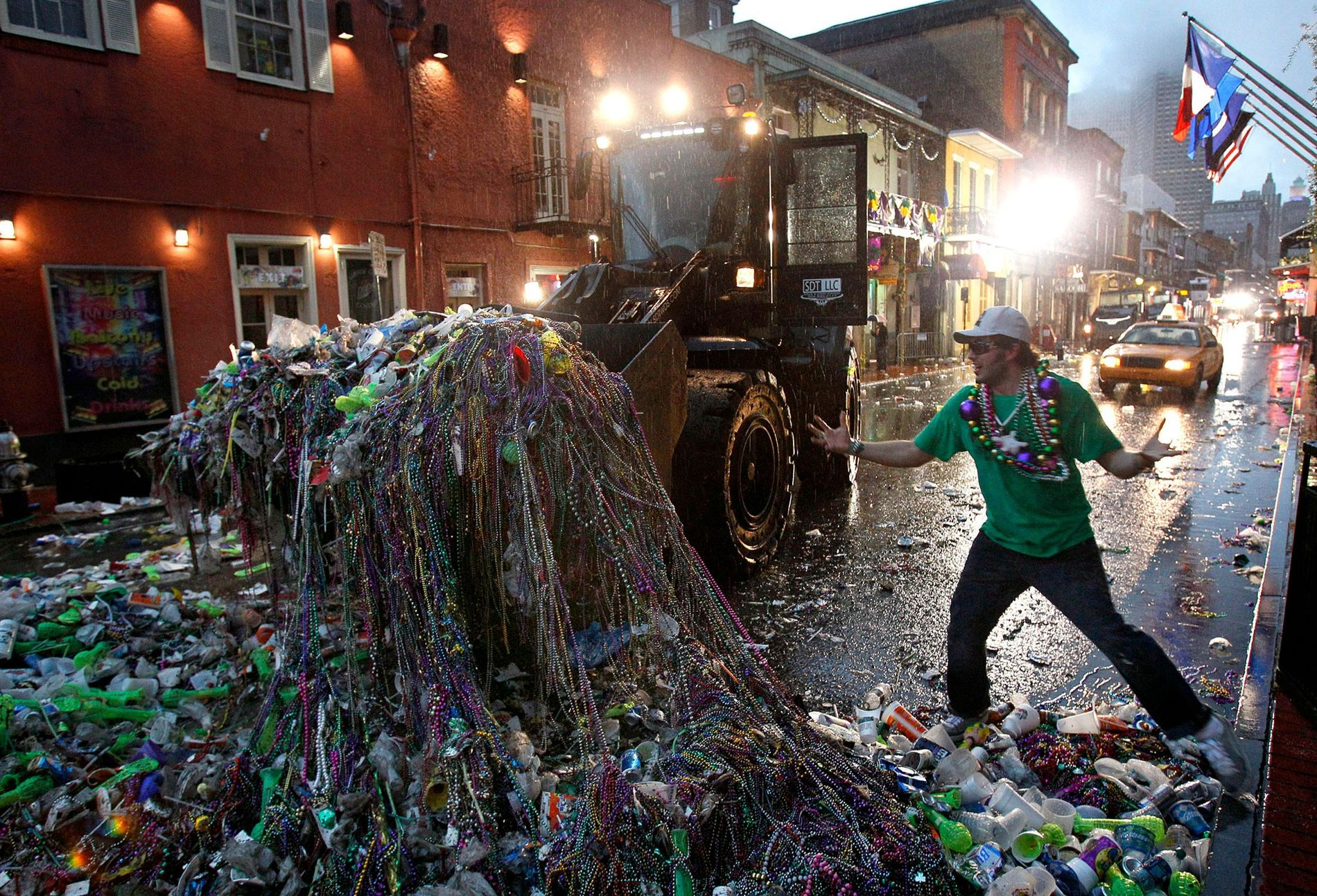 Mardi Gras reveler Mike Turpin, whose night still isn't over, watches as a front loader collects ...