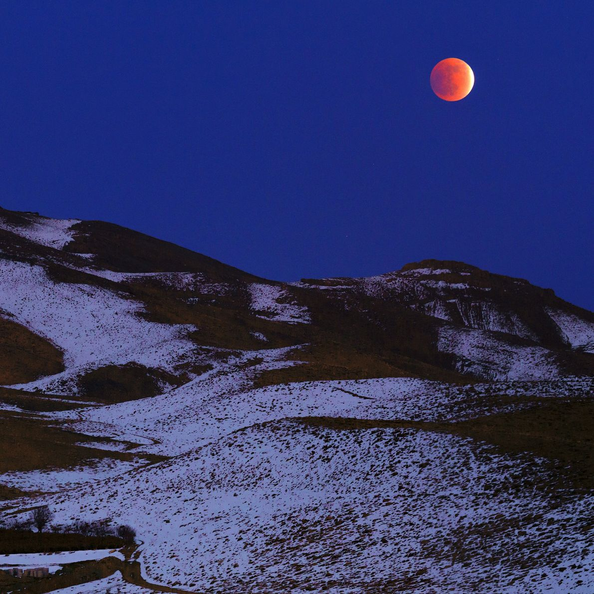 The total lunar eclipse of December 2011 glows in the evening sky over the Zagros Mountains ...