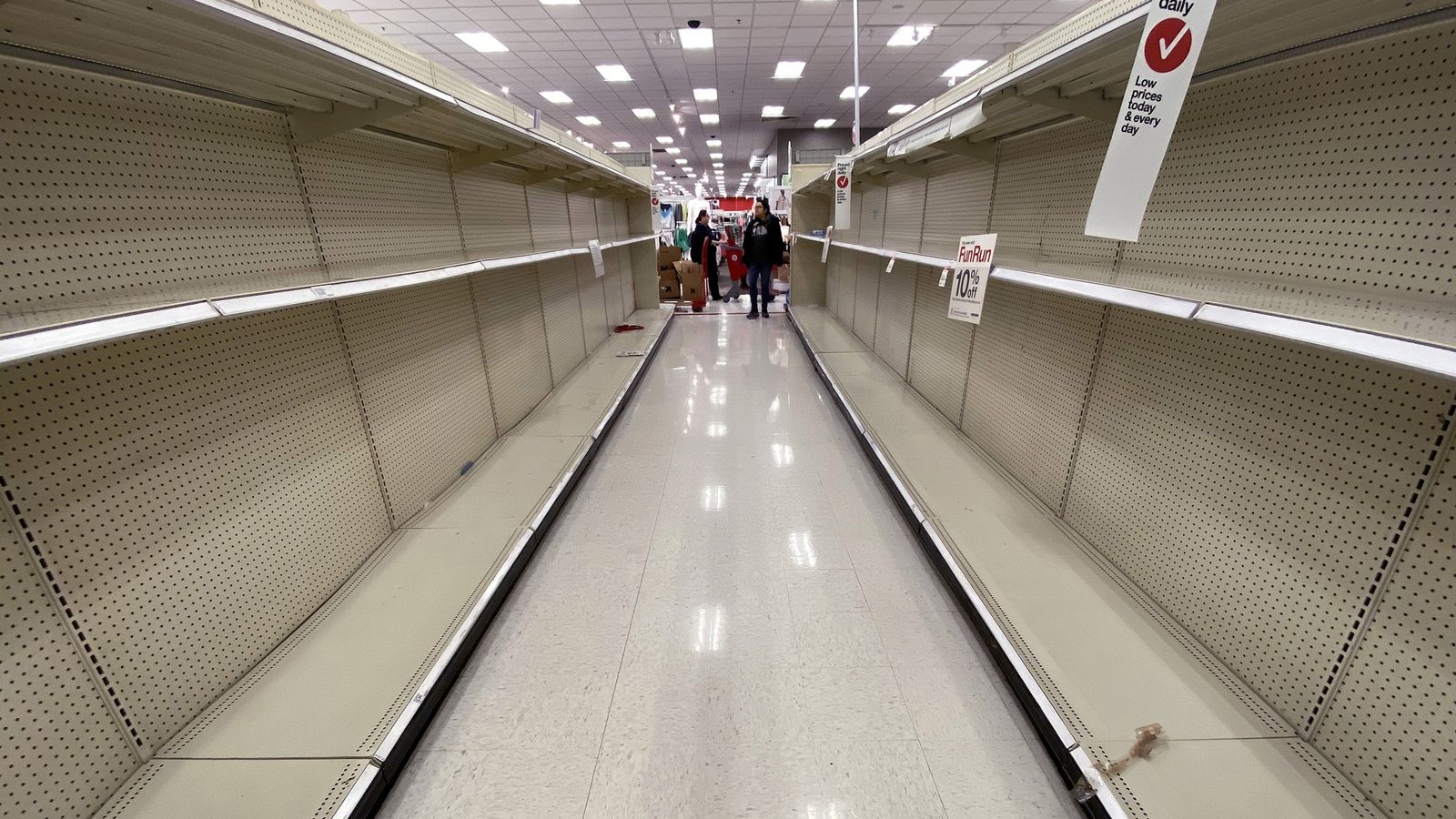 Shelves normally stocked with hand wipes, hand sanitiser, and toilet paper sit empty at a Target ...