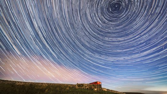 A composite image shows Perseid meteors cutting through the stars wheeling over Yorkshire Dales National Park ...