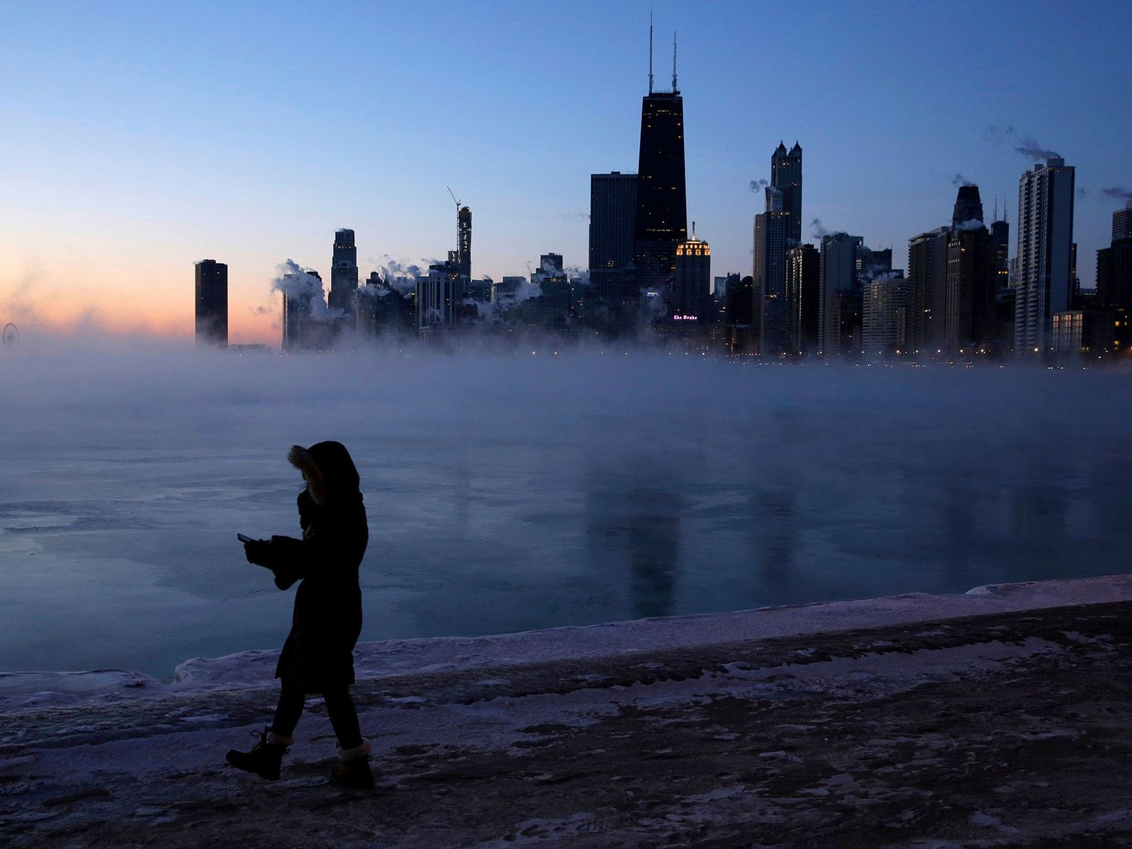 A person walks along Chicago's lakeshore on Wednesday where Arctic air from the polar vortex has ...