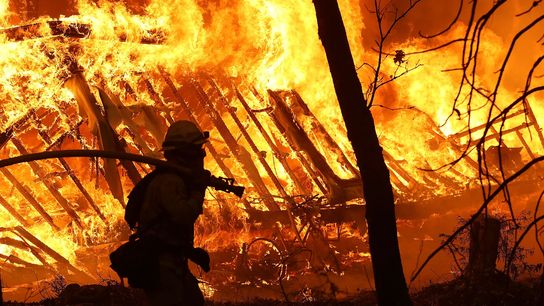 A Cal Fire firefighter monitors a burning home as the Camp Fire moves through the area ...