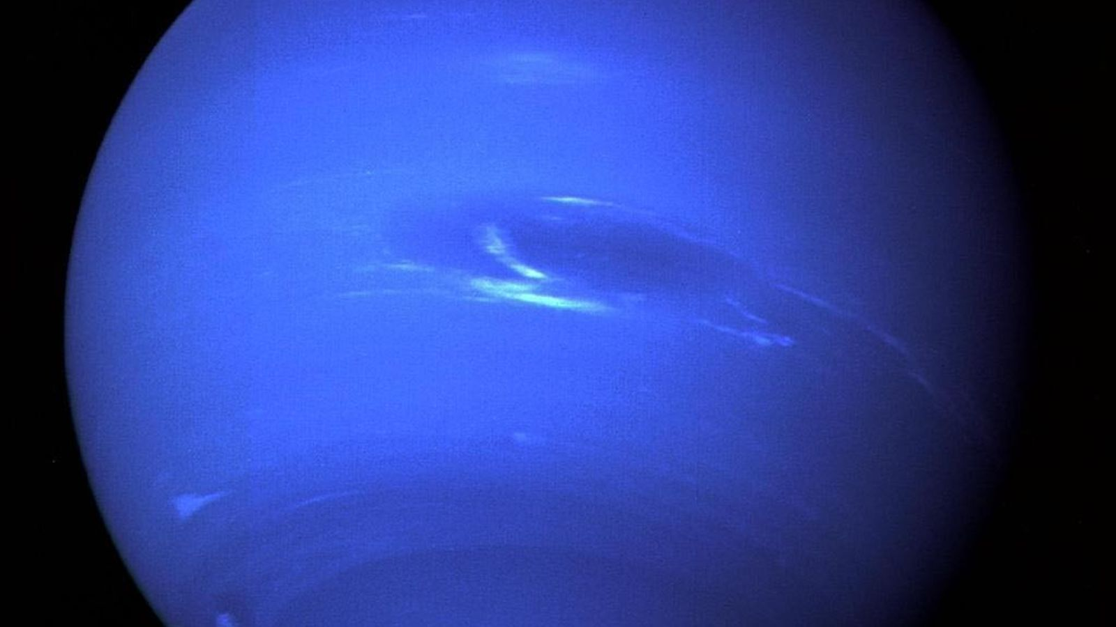 The eighth planet Neptune gleams bright blue in this image from Voyager 2, taken from a ...