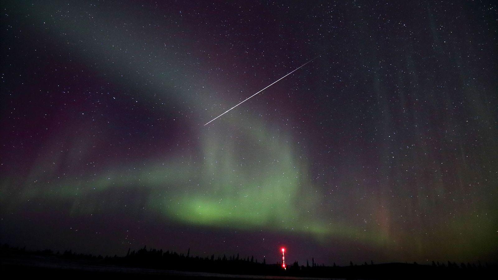 A shooting star cuts across auroras in a November night sky.