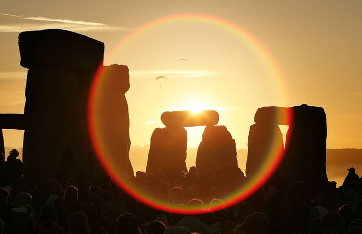 People watch the midsummer sun as it rises over the megalithic monument of Stonehenge on June ...