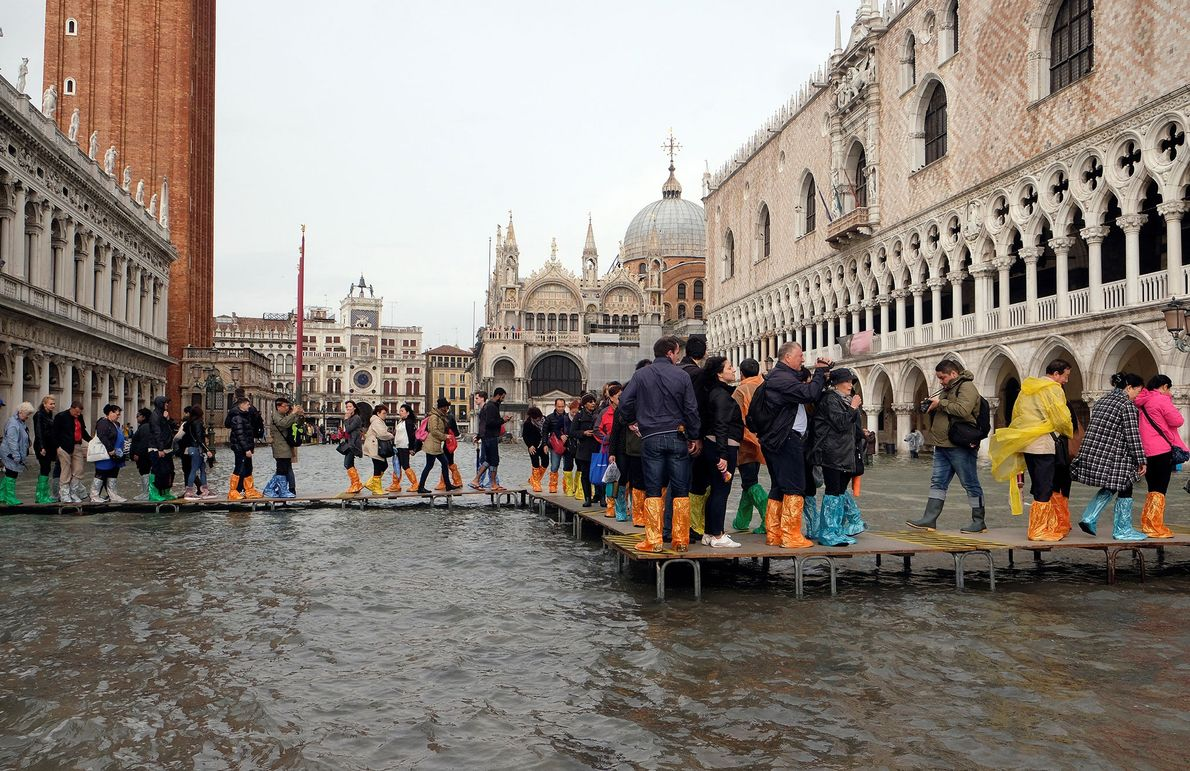 People walk on a catwalk in a flooded St. Mark's Square during a period of seasonal ...