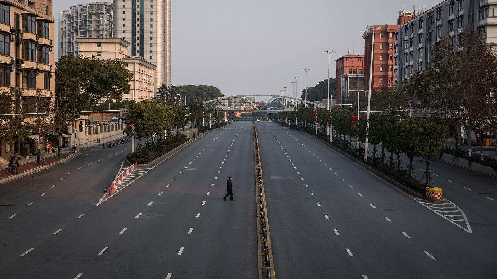 A man crosses an empty highway on February 3, 2020 in Wuhan, China. The number of ...