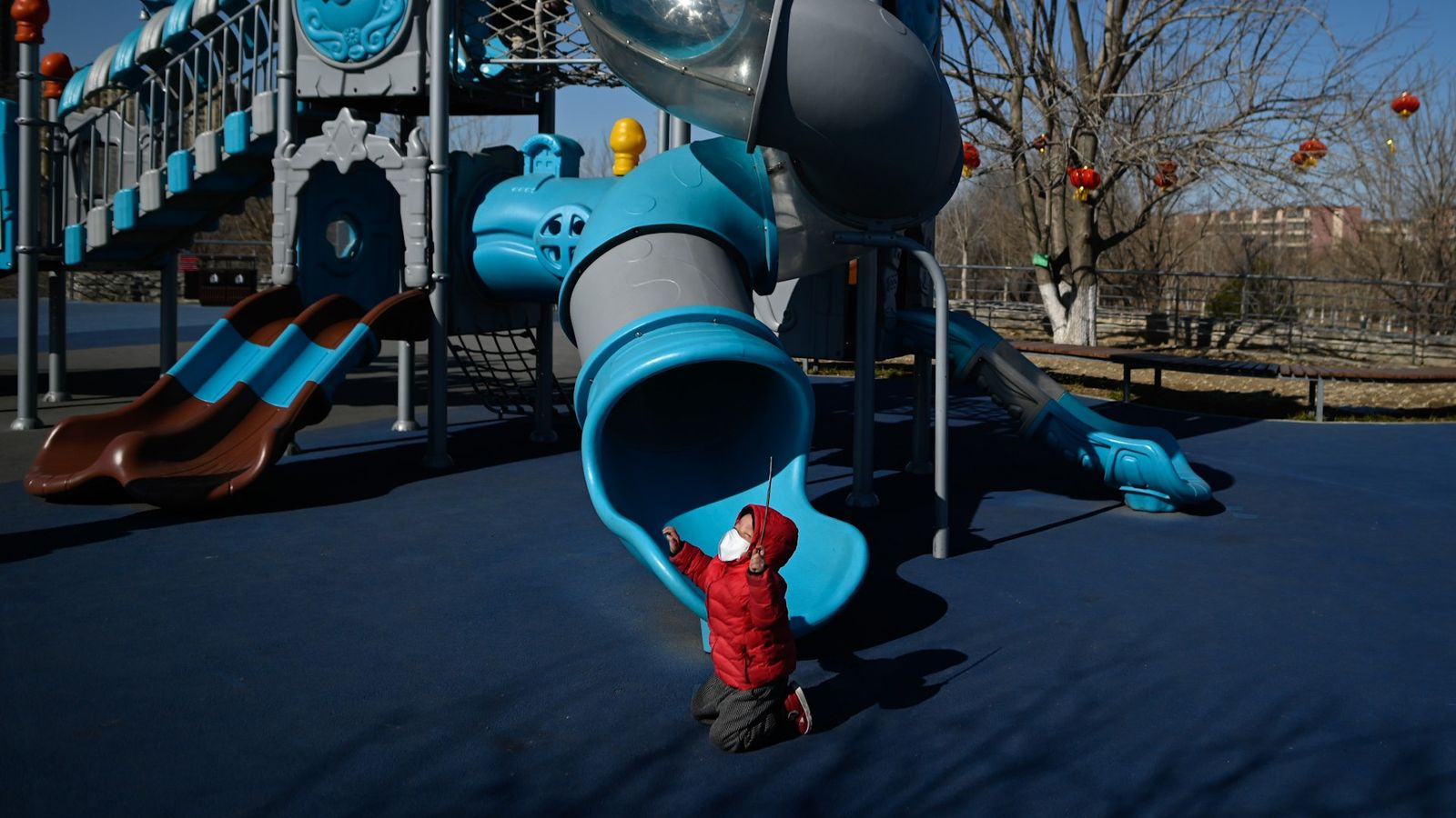 A boy wearing a face mask plays at a playground along a street in Beijing, China.