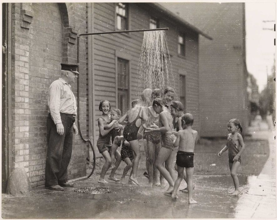 Children cool off from summer heat under a pavement spray outside a Connecticut firehouse.