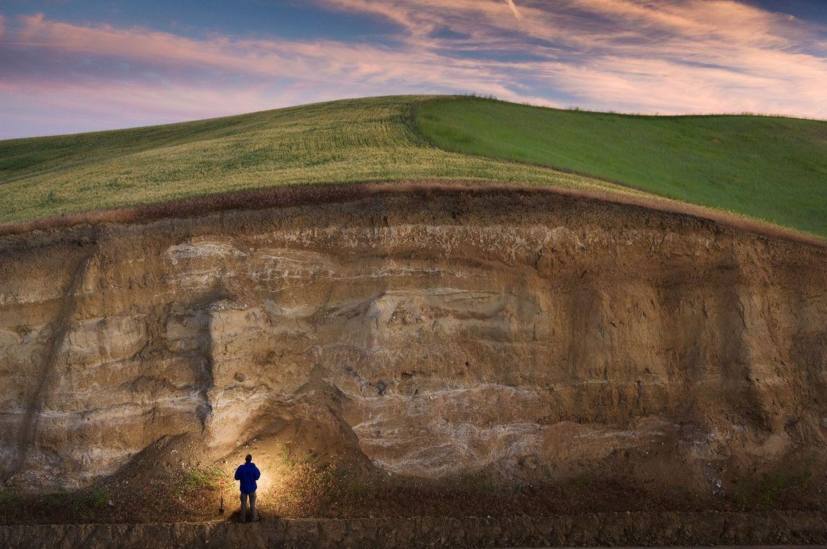 John Reganold of Washington State University stands by a deep road cut in eastern Washington's Palouse …