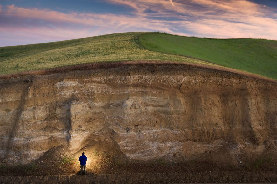 John Reganold of Washington State University stands by a deep road cut in eastern Washington's Palouse ...