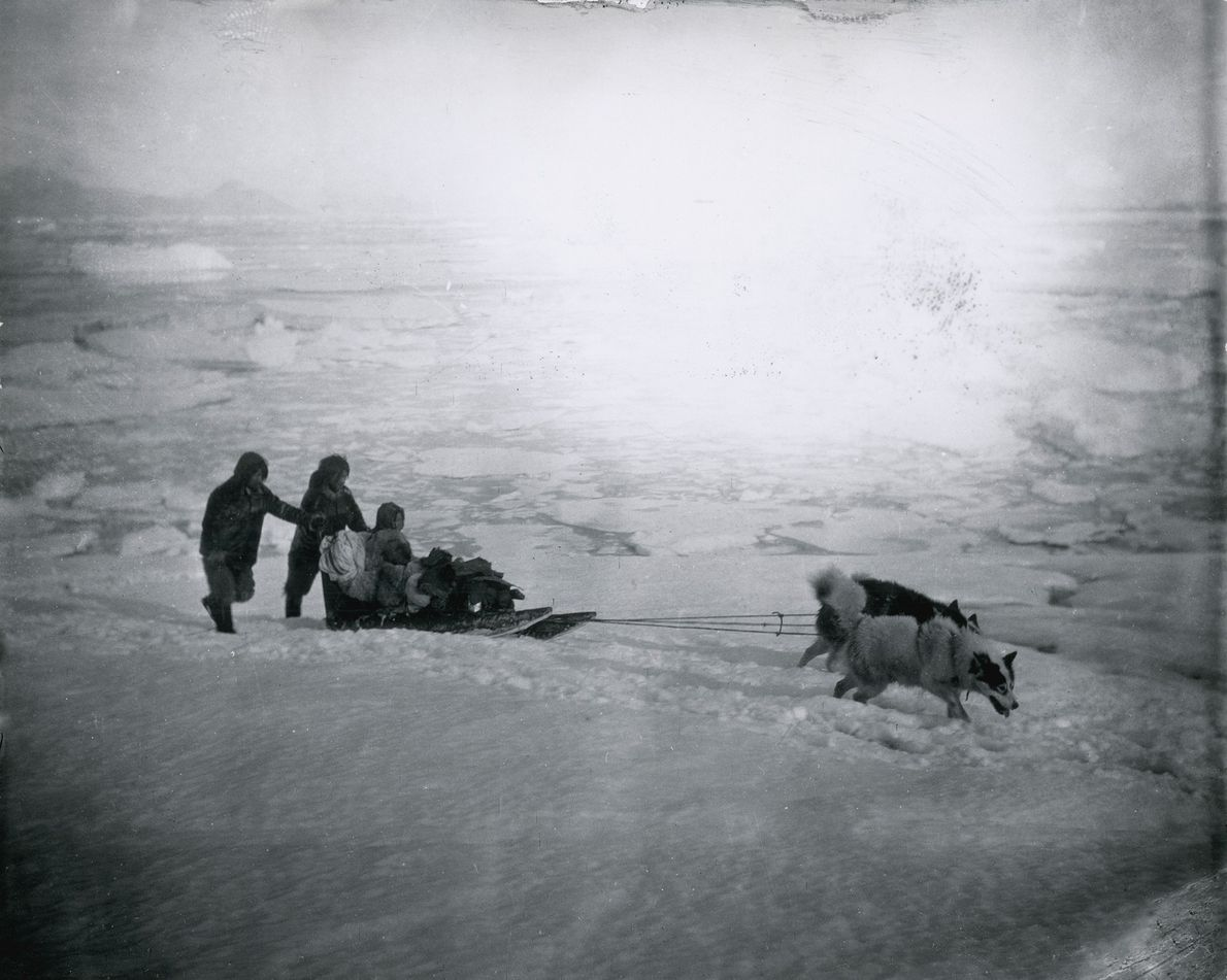 Inuit people and their dogs travel by sledge. The photo was first published in Northward Over ...