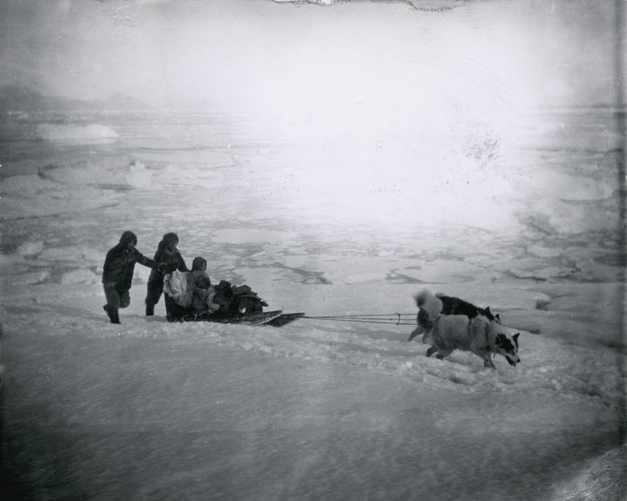 Inuit people and their dogs travel by sledge. The photo was first published in Northward Over …