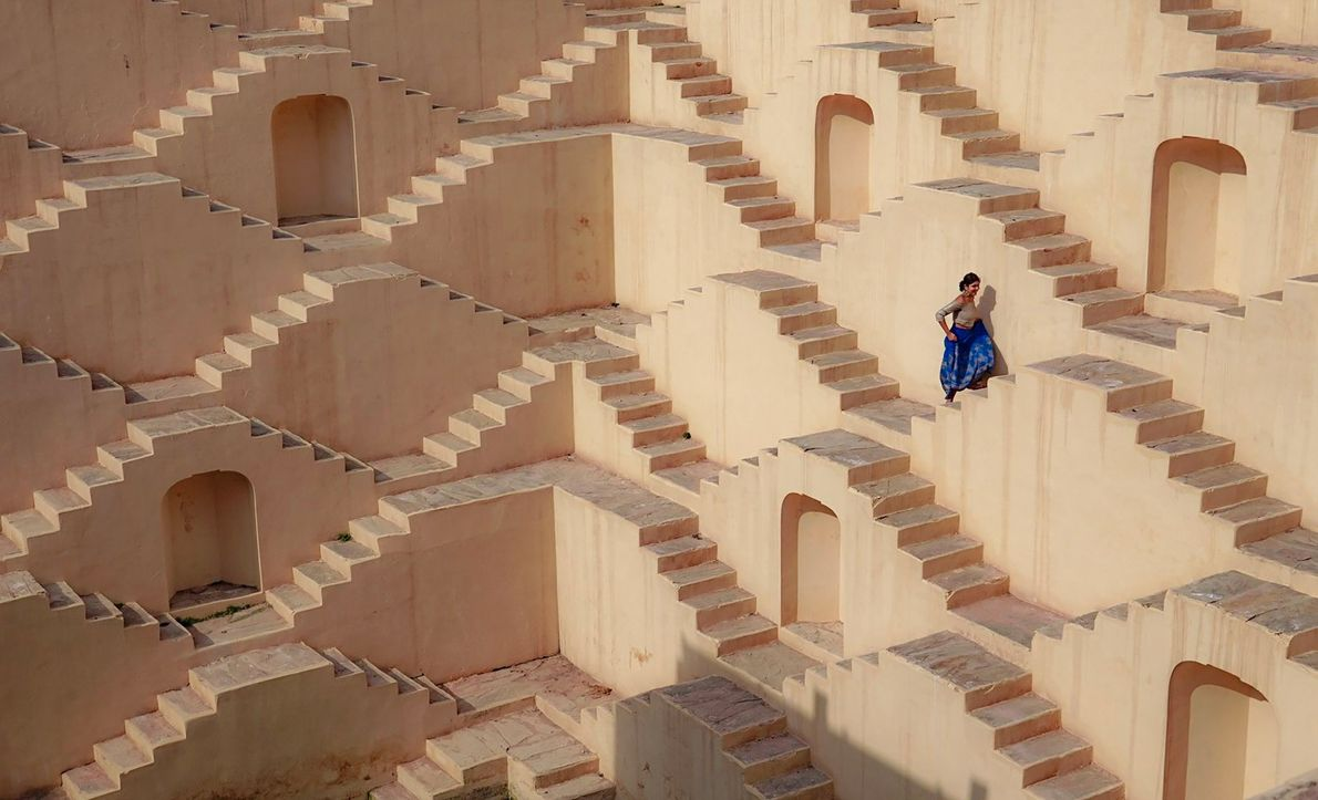 A woman's rich blue clothes stand out among the Escher-like staircases of Panna Meena ka Kund ...