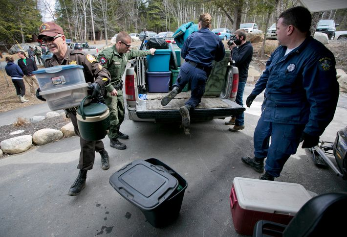 Law enforcement officials unload items removed from Knight's camp in the dense woods near Rome, Maine.