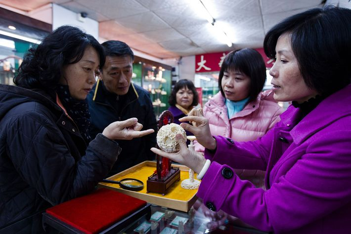 Shoppers admire an ivory ornament at a state-owned ivory business in Guangzhou, China, in 2012. This ...