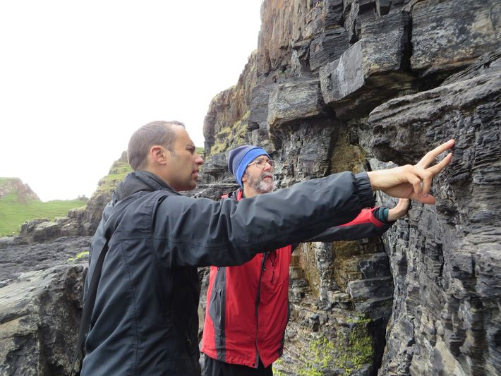 Steve Brusatte (left) and Mark Wilkinson examining the cliff face directly adjacent to the tracksite.