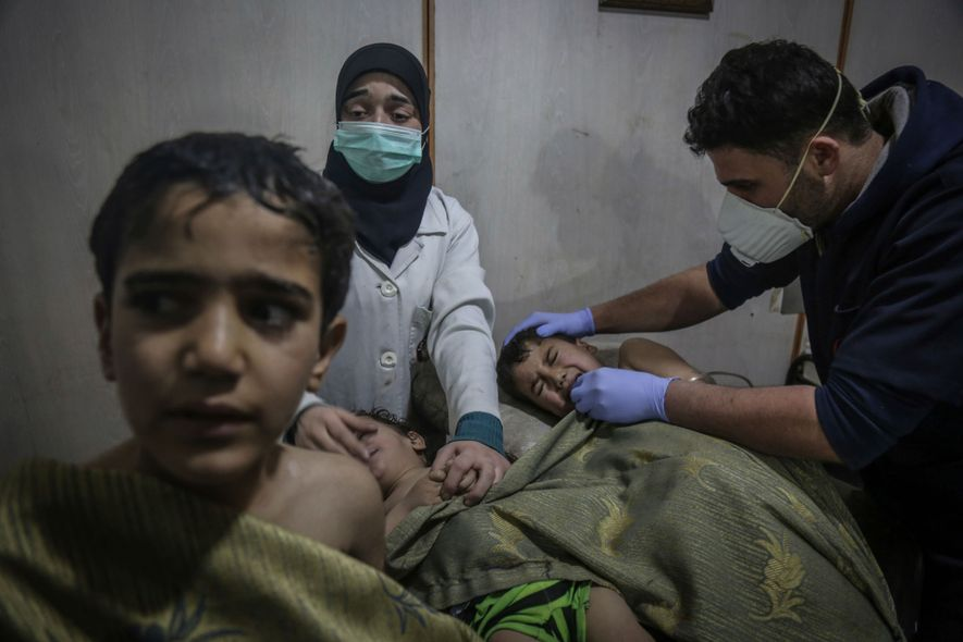 """Children receive first aid after an apparent chemical attack. """"The smell of chlorine was overwhelming,"""" says ..."""