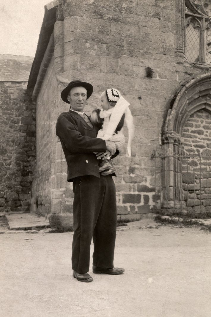 A Breton father carries his daughter while standing in a churchyard in Finistère, France, in the ...