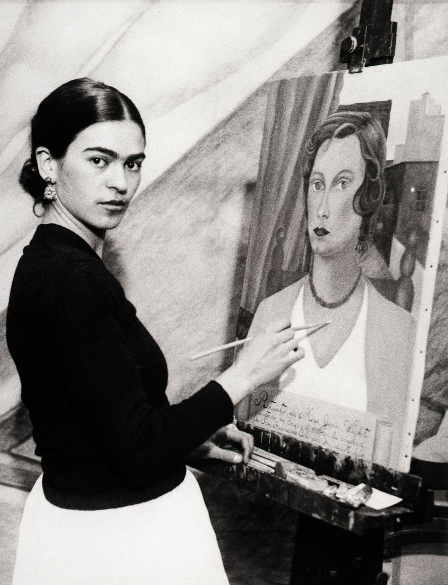 Frida Kahlo poses next to a portrait of a socialite she painted while her husband worked ...
