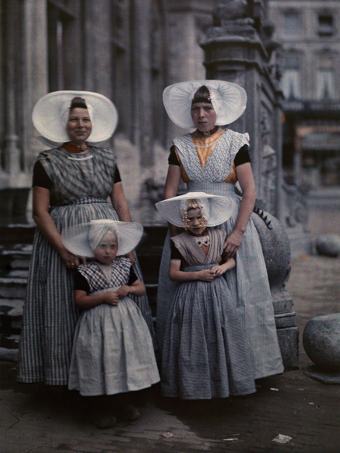 Two women pose with their daughters in their traditional Zeeland clothing in the Netherlands. Protestant women ...