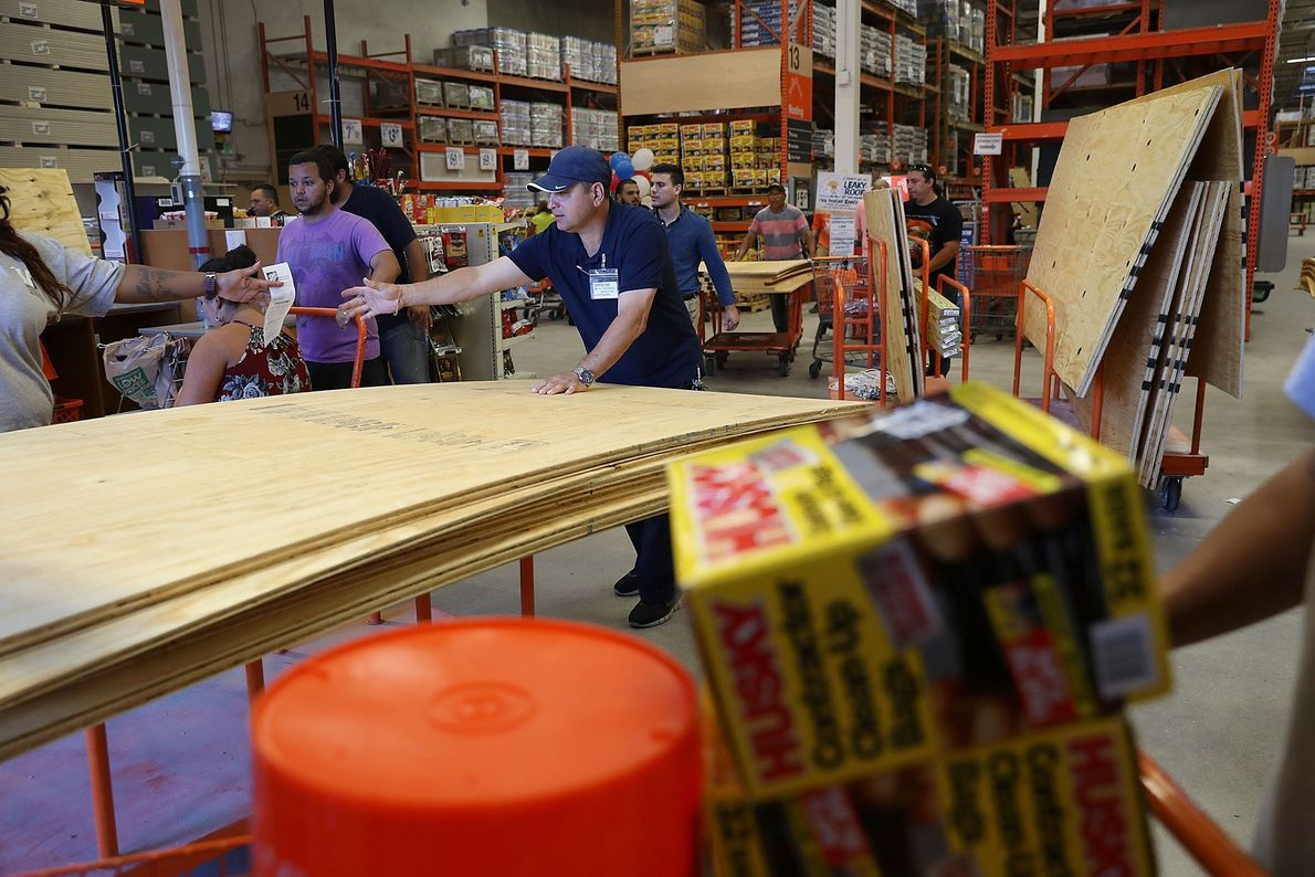 People purchase plywood at The Home Depot as they prepare for Hurricane Irma on September 6 ...