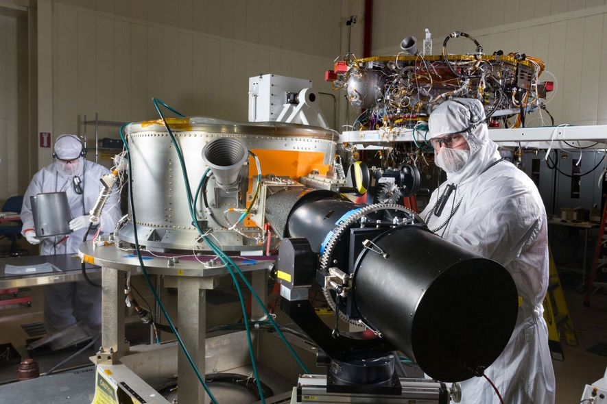 Engineers work on NASA's InSight spacecraft in a clean room in 2015, during the mission's assembly ...