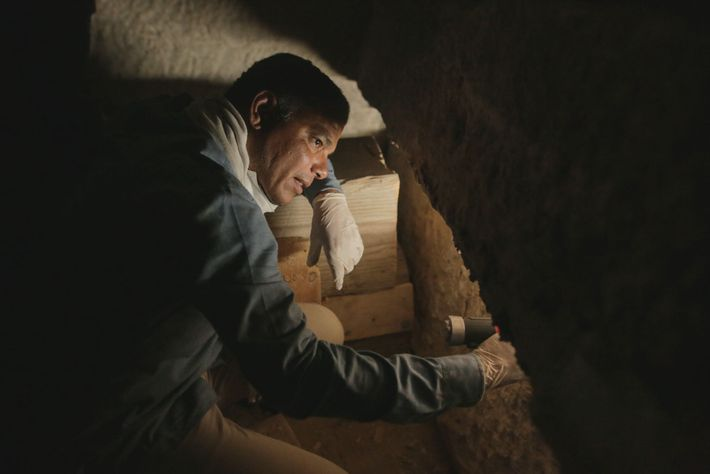 Ramadan Hussein peers inside a stone sarcophagus in search of mummies. The team discovered more than ...