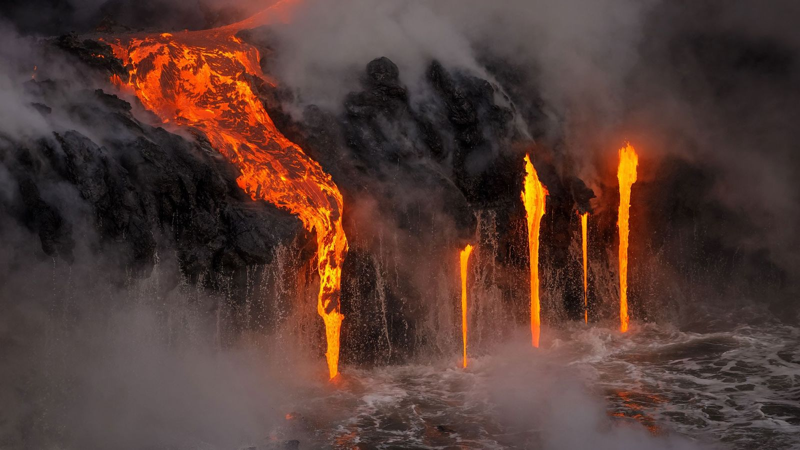 A river of lava bursts out of the side of the mountain and spills into the ...