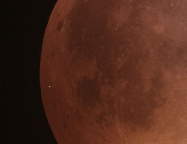 "A close-up of the darkened face of the ""blood moon"" shows the flash from the meteor ..."