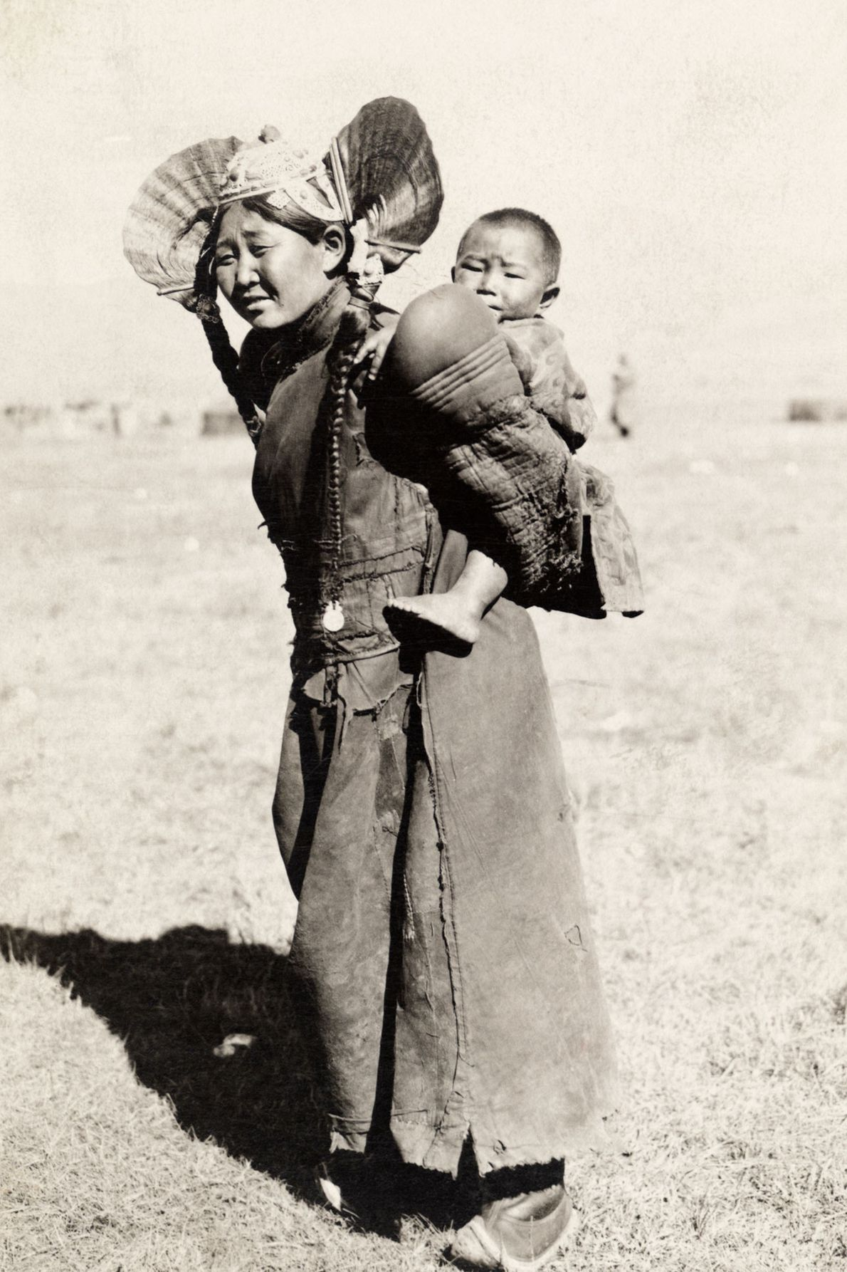 Dressed in traditional clothing, a woman in northern Mongolia carries her son on her back.
